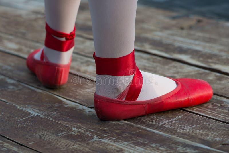 Chaussures de ballet rouges avec les chaussettes blanches dans la ballerine photographie stock