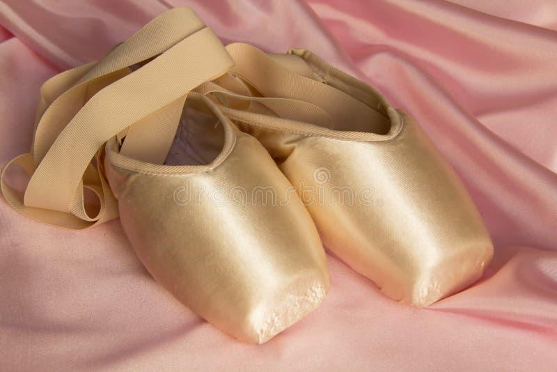 Chaussures de ballet sur le rose en soie photo libre de droits