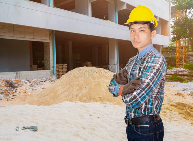 Chaussures de bras d'ingénierie usure casque sécurité jaune extérieur et couverture de sable chantier de construction de la pelle photographie stock
