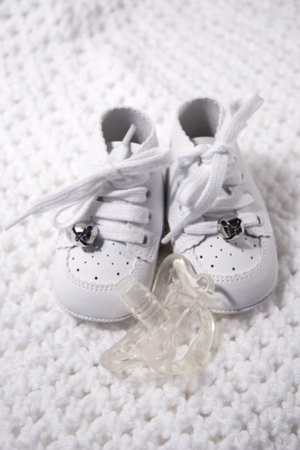Chaussures de chéri avec le pacificateur photographie stock libre de droits