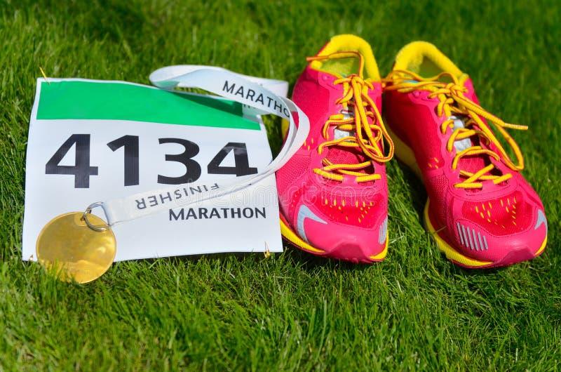 Chaussures de course, bavoir de course de marathon (nombre) et médaille de finisseur sur le fond d'herbe, photos stock