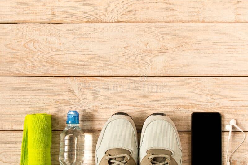 Chaussures de course et accessoires gris de forme physique sur le fond en bois L'espace vide des textes photographie stock