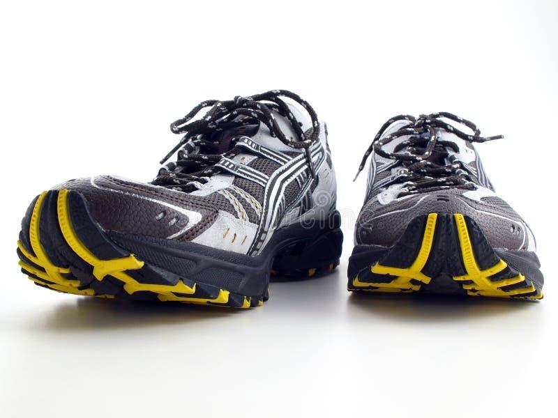 Chaussures de course rayées sur la vue de face blanche image libre de droits
