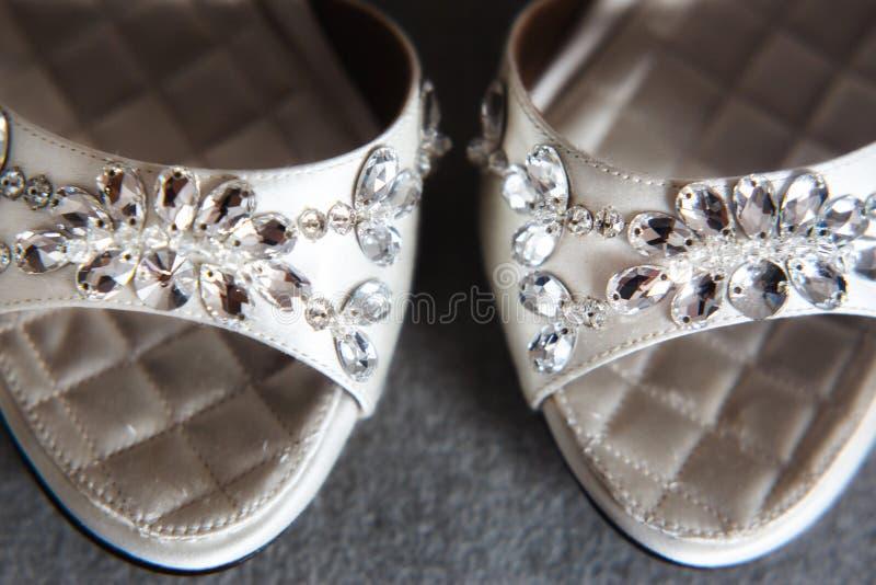 Chaussures de mariage avec des bijoux sur le plancher gris photographie stock libre de droits