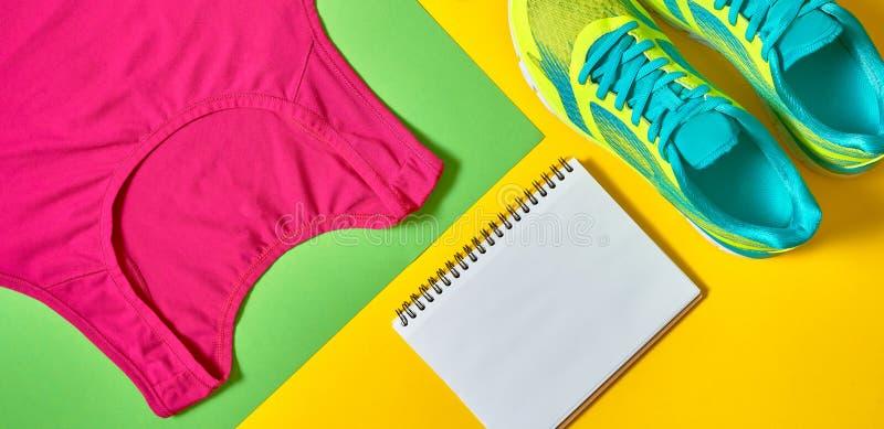 Chaussures de sport, woman' ; soutien-gorge de dessus de s, carnet vide blanc et corde à sauter sur le backgroundon jaune et  image stock