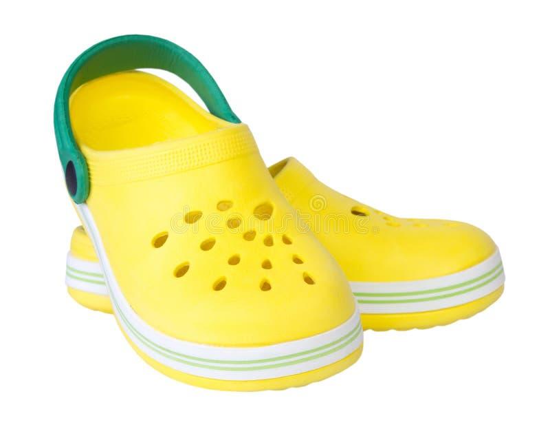 Chaussures en caoutchouc jaunes du ` s d'enfant de paires d'isolement image stock