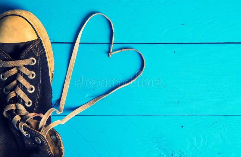 Chaussures en caoutchouc sales sur le fond en bois de coeur image libre de droits