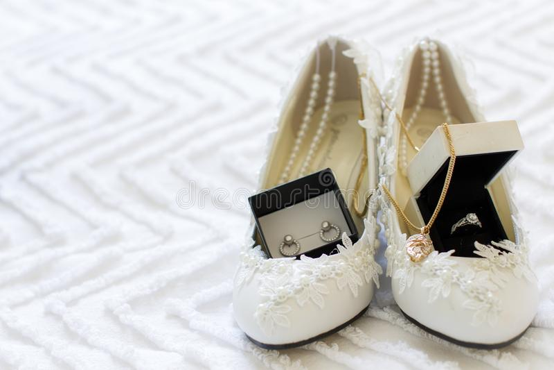 Chaussures et bijoux de jeunes mariées sur le lit photo stock