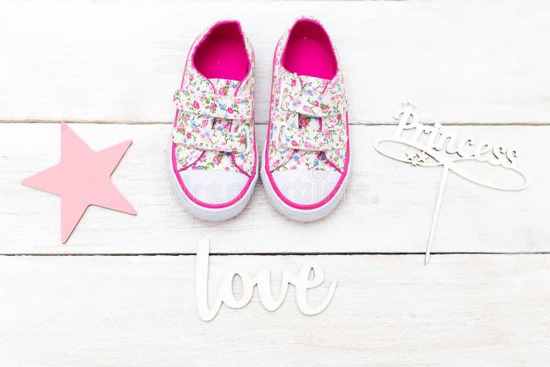 Chaussures et inscriptions de rose du ` s d'enfants sur un backgro en bois blanc images libres de droits