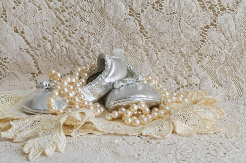 Chaussures et perles de bébé sur le mouchoir de dentelle images stock