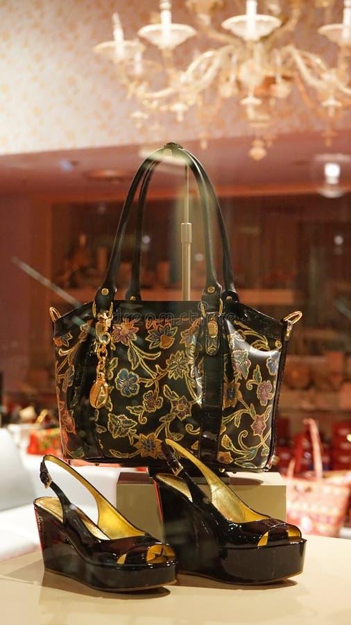 Chaussures et sac à main sur l'affichage du magasin de luxe, fond intérieur rose photographie stock libre de droits