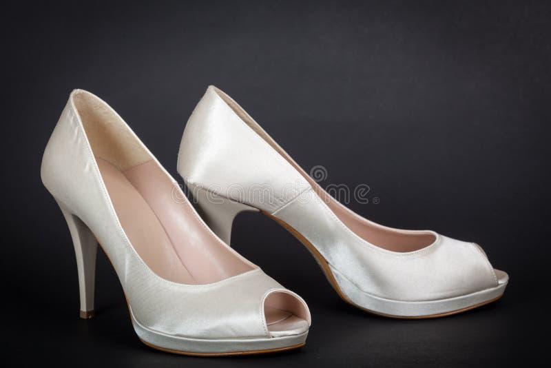 Chaussures femelles blanches élégantes sur le fond foncé photographie stock libre de droits