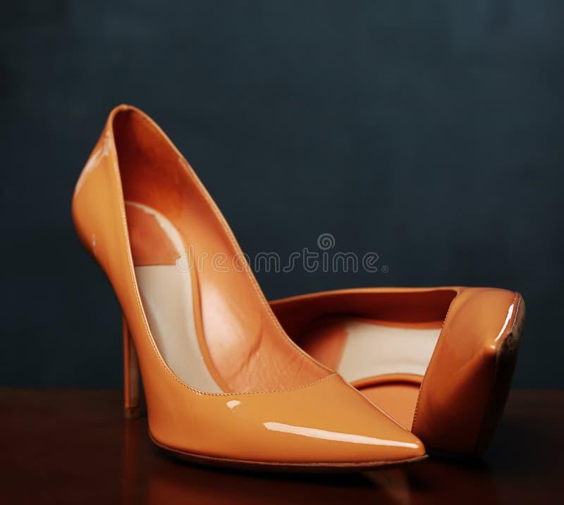 Chaussures femelles jaunes sur la surface en bois foncée photos stock