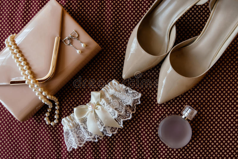 Chaussures, jarretière, parfum, collier et embrayage du ` s de jeune mariée image stock