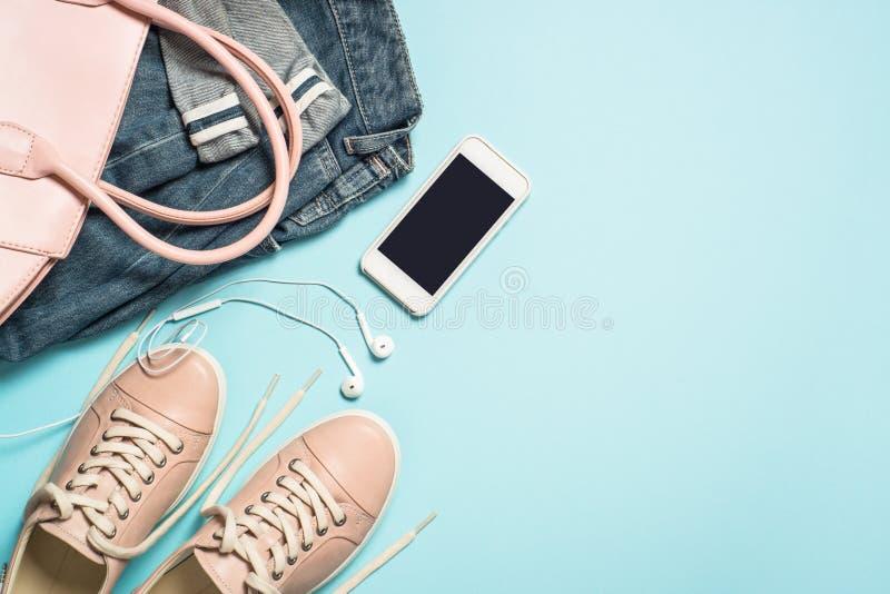 Chaussures, jeans, sac ? main, smartphone et parfum roses r?gl?s de tissu de mode de femme sur le fond bleu photos stock