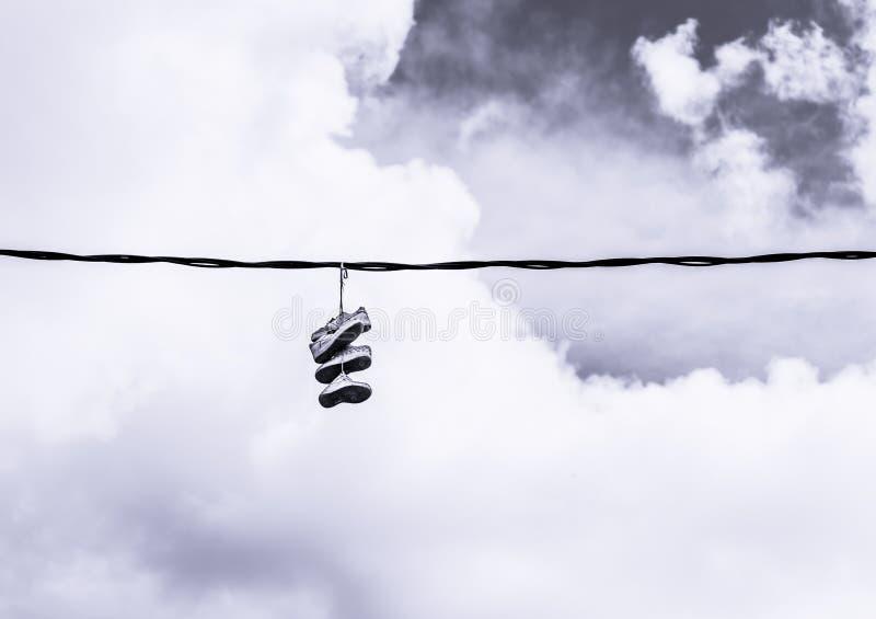 Chaussures jetées en l'air au-dessus d'une ligne à haute tension photographie stock libre de droits