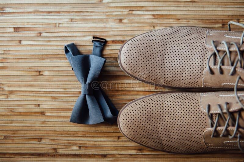 Chaussures les épousant élégantes de brun de partie, noeud papillon se trouvant sur un plancher en bois Marié d'accessoires photo stock