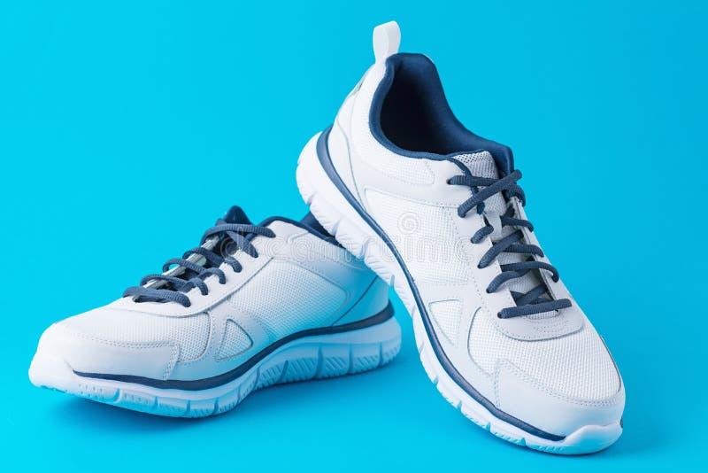 Chaussures masculines de sport de mode sur un fond bleu Espadrilles élégantes d'homme pour la forme physique, fin  photo stock