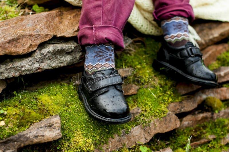 Chaussures noires avec les chaussettes colorées sur des jambes d'enfant images libres de droits