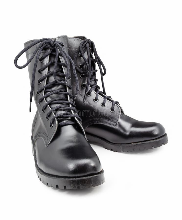 Chaussures noires d'armée d'isolement sur les milieux blancs photo libre de droits