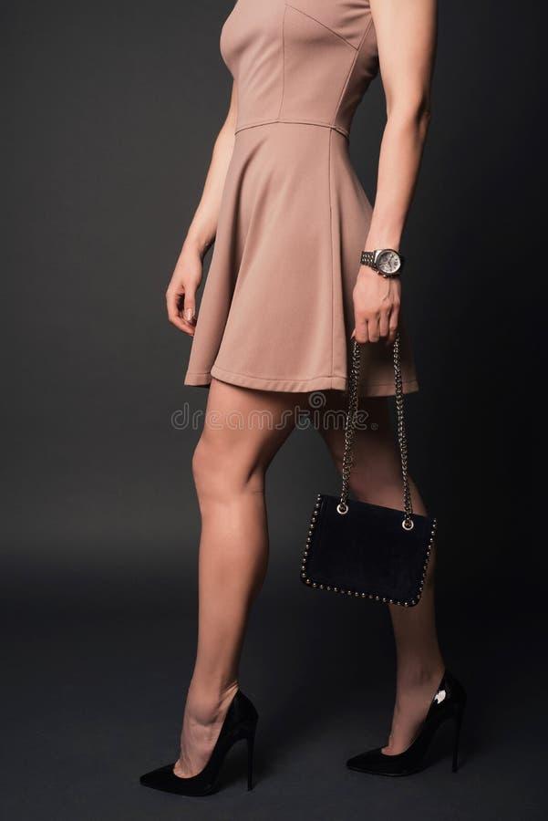 Chaussures noires de port de robe de fille de mode de style tenant le petit sac à main avec des détails images stock