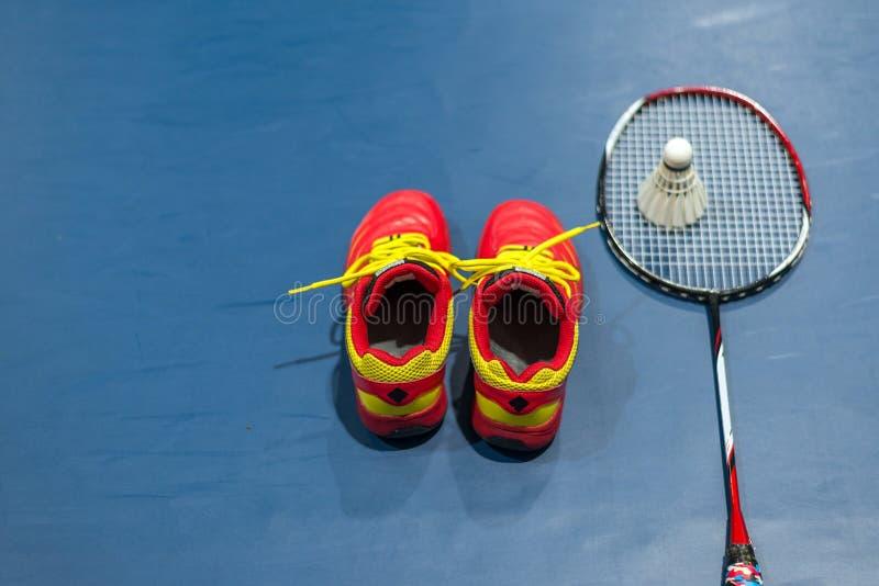 Chaussures rouges de badminton avec le volant et la raquette brouillés sur la cour photographie stock libre de droits