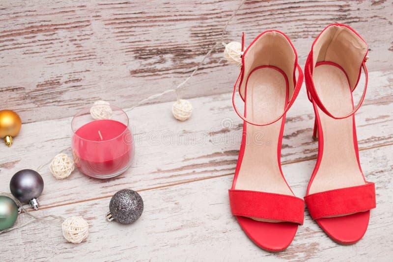 Chaussures rouges de suède sur un fond en bois, les ornements de fourrure-arbre et la bougie Concept de mode photo libre de droits