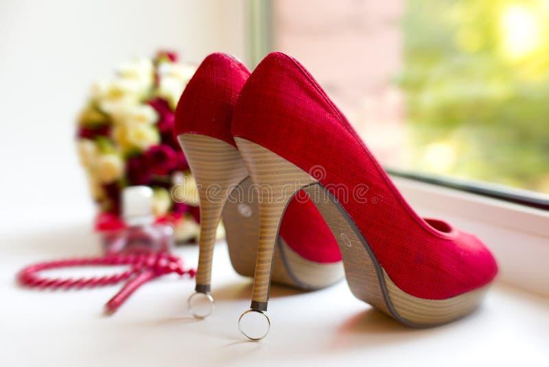 Chaussures rouges ou cramoisies de tissu sur des anneaux de noces d'argent photographie stock