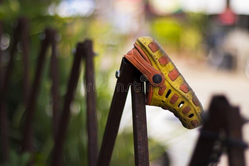 Chaussures sales d'enfant accrochant sur la barri?re pour s?cher image libre de droits
