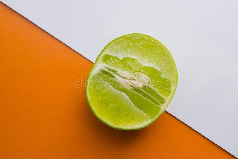 Chaux fraîche demi sur le fond orange et blanc photos stock