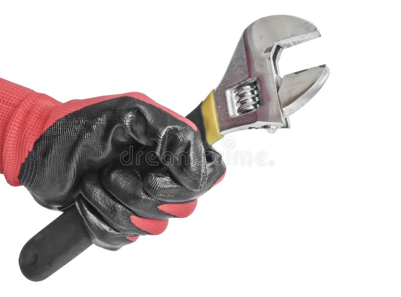 Chave ajustável na mão de um homem em uma luva de trabalho vermelha Ferramenta do serralheiro fotos de stock royalty free