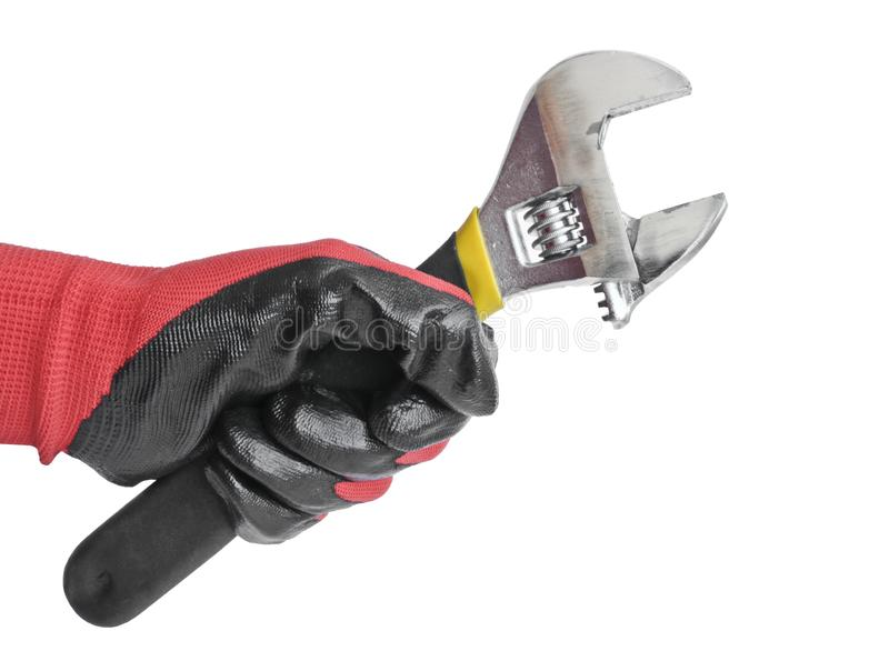 Chave ajustável na mão de um homem em uma luva de trabalho vermelha Ferramenta do serralheiro fotos de stock