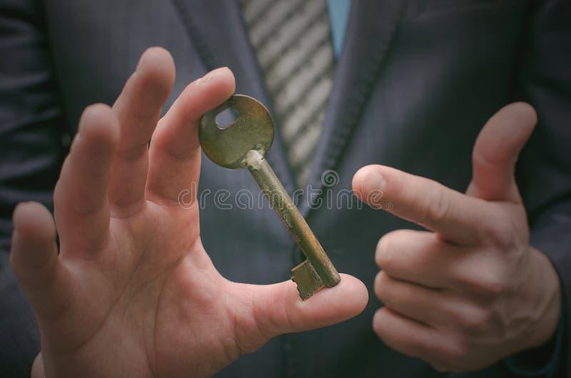 Chave ao conceito do sucesso Homem de negócios que realiza nas mãos uma chave oxidada velha imagens de stock