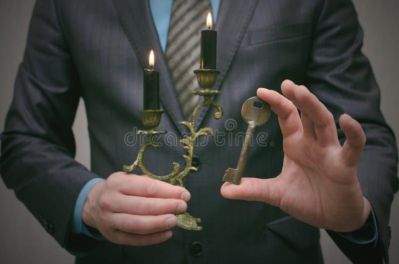 Chave ao conceito do sucesso Homem de negócios que realiza nas mãos uma chave oxidada velha e uma vela ardente no castiçal fotografia de stock