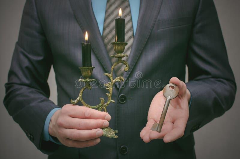 Chave ao conceito do sucesso Homem de negócios que realiza nas mãos uma chave oxidada velha e uma vela ardente no castiçal fotos de stock