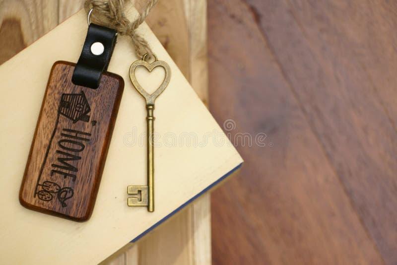 Chave da casa do vintage com o keyring de madeira da casa no fundo de madeira da placa, conceito da propriedade, espaço da cópia foto de stock royalty free