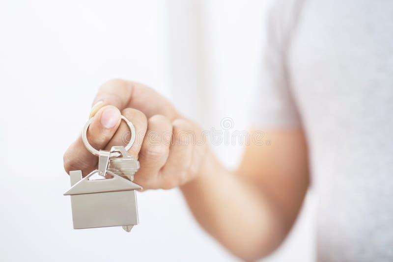 Chave da casa da terra arrendada da mão dos povos na porta-chaves dada forma casa conceito para o condomínio de compra do alojame foto de stock
