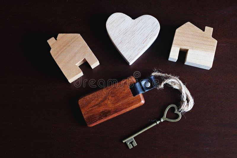 Chave da forma do coração com o keyring de madeira da casa, modelo de madeira do coração e figura decoração da casa, conceito doc imagens de stock