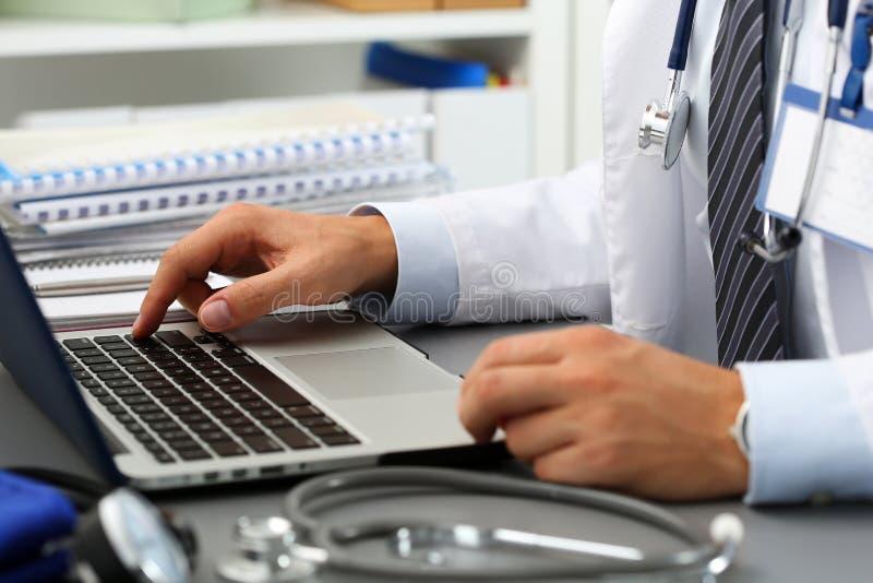 Chave da imprensa da mão do doutor da medicina no teclado de laptop fotografia de stock
