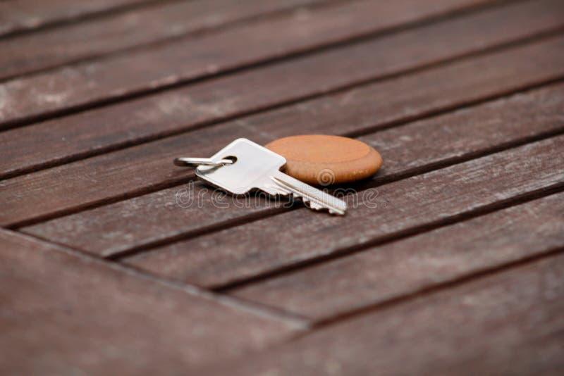 Chave da série de hotel com a corrente de relógio de madeira para a sala na tabela de madeira Chave de sala na textura e no fundo imagens de stock royalty free