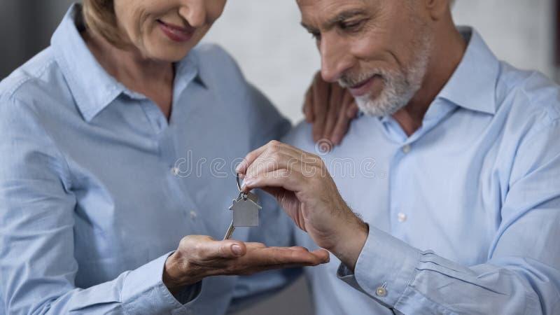 Chave de doação masculina de envelhecimento da casa à senhora de sorriso, compra dos bens imobiliários, hipoteca fotografia de stock