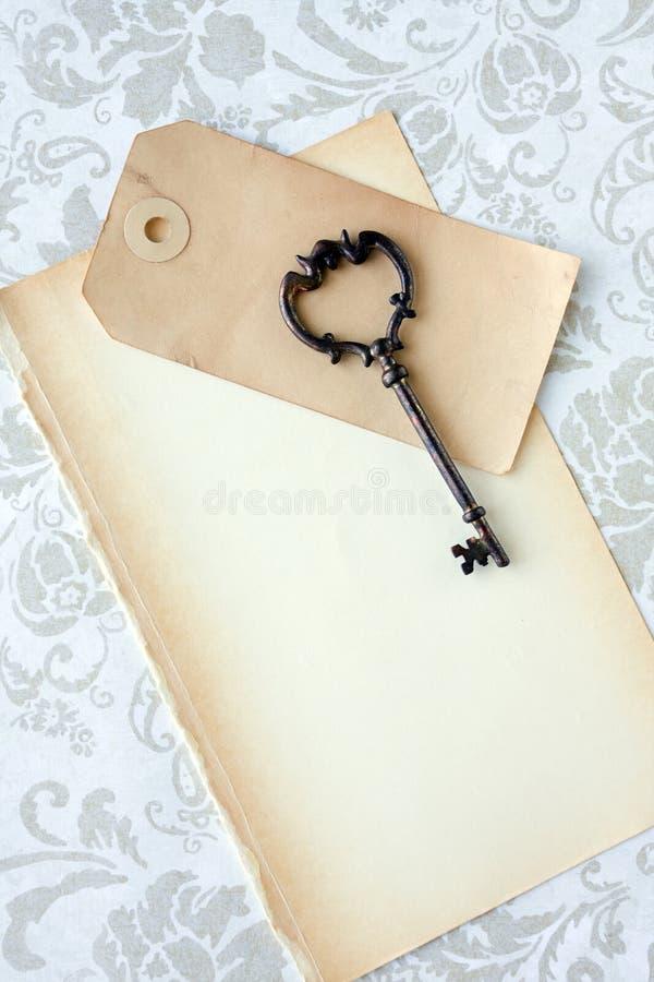 Chave de esqueleto velha e papel fotos de stock