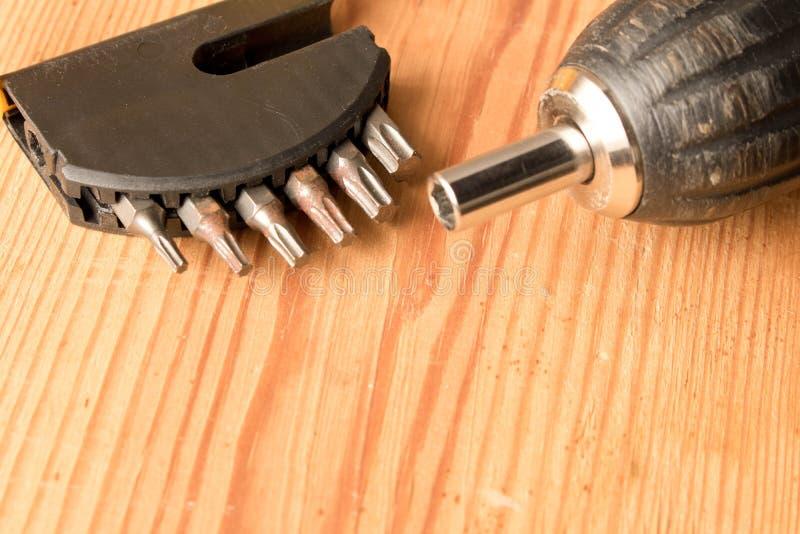Chave de fenda e um grupo de bocados em uma tabela de madeira O conceito de foto de stock