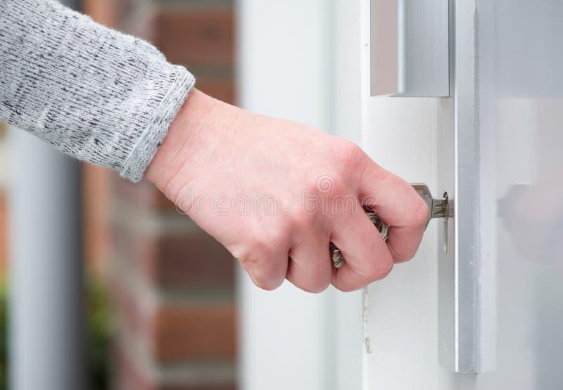 Chave de introdução fêmea da mão na porta imagem de stock
