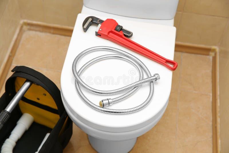Chave de tubulação e mangueira flexível na tampa do assento da sanita imagem de stock
