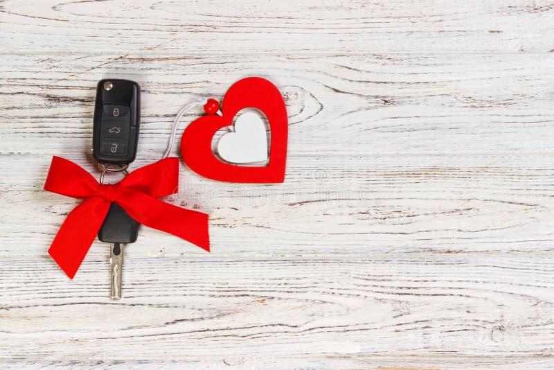 Chave do carro com um ADN vermelho da fita um coração na tabela de madeira branca Dando o presente ou o presente para o dia ou o  imagens de stock royalty free