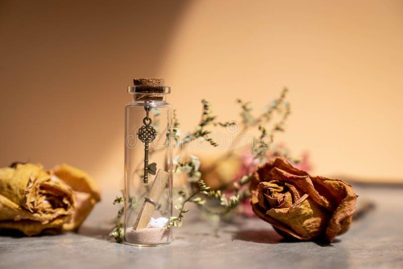 A chave do metal do vintage e a letra do papel rolam na garrafa de vidro fotos de stock