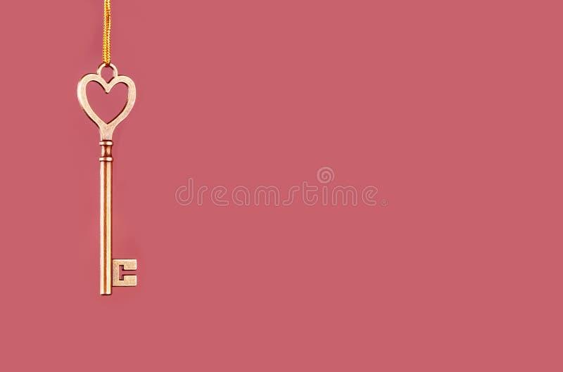 Chave dourada à suspensão em um fundo cor-de-rosa fotos de stock