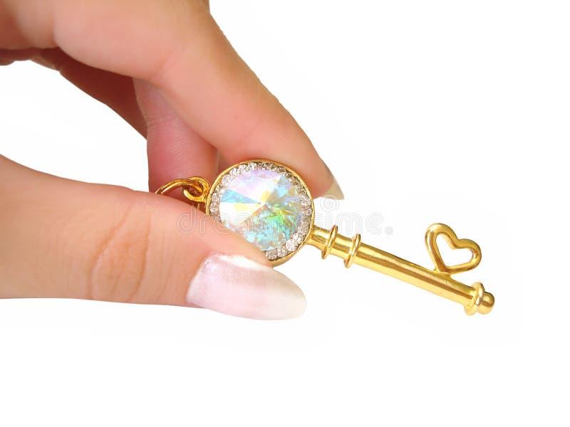 A chave dourada na mão isolou-se imagem de stock royalty free