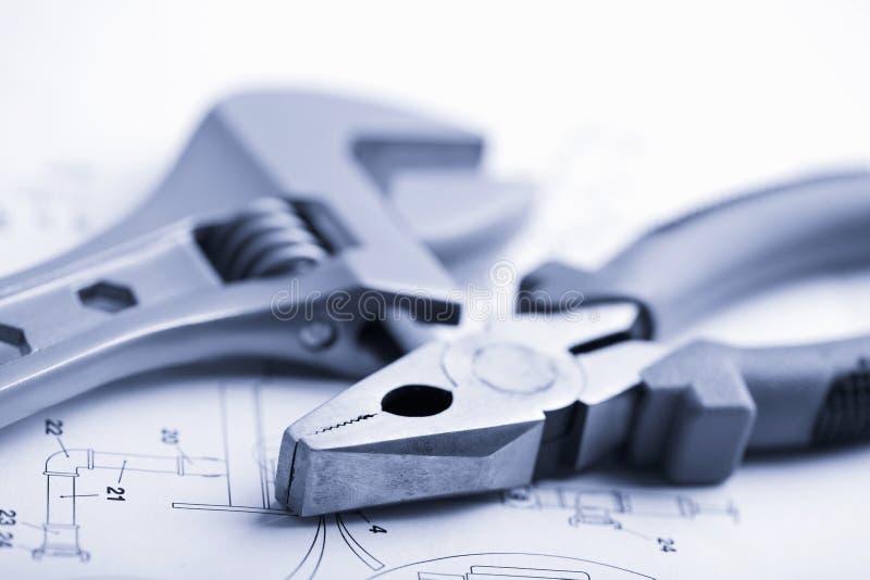 Chave e alicates sobre o desenho técnico imagens de stock